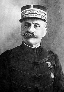 An elderly gentleman with a handlebar-style moustache. He is wearing a peaked cap highly decorated with light-coloured braiding. He wears a dark, high-collared jacket, with regularly spaced horizontal bands of braiding. On his left breast, he wears a medal on a ribbon above a star.