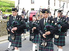 A group of men and women wearing traditional highland dress are playing the bagpipes as they walk down a road. A member of the group is playing a large red drum. A white, two storey building is in the background.