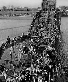 Black-and-white photo of people crossing a river via a destroyed brdige