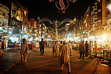 picture taken in evening, having a bazaar with people walking around, and food shops.
