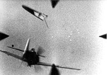 Gunsight view: In the bottom left, a fighter aircraft is seen from the rear, its tail plane is separated and above it, a cluster of bright tracer can be seen picture center-right.