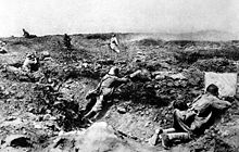 In the foreground three German soldiers behind cover engage attacking French soldiers