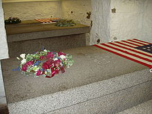 3 marble sarcophagi, one in the foreground, 2 in the background are seen. 2 are seen with flags of the United States at the top.