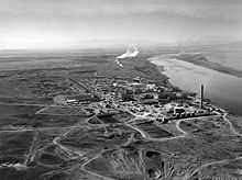 A cluster of industrial structures lie on a flat plain by a big river. The structures include a few low rectangular buildings, many smaller buildings, cylindrical tanks of varied sizes, and a tall smokestack. Several roads connect the cluster to other parts of the plain. Smoke or steam rises from two places further upriver.