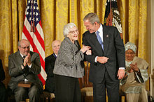 A color photograph of Harper Lee smiling and speaking to President George W. Bush while other seated Medal of Freedom recipients look on