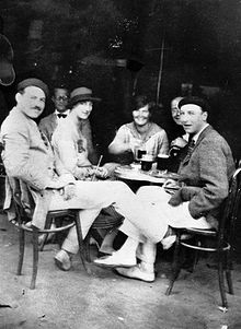 three men, dressed in light colored trousers and wearing hats, and two women, wearing light colored dresses, sitting at a sidewalk table