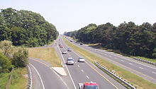 A highway passes beneath the camera and continues straight into the horizon. It is surrounded by forests on either side and contains no guardrail to separate opposite flows of traffic.