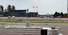 A building on a clear day. It is situated amongst considerable asphalt, with trees in the bacground. Two flag poles are in front of the building, an Ontario and Canada flag. The building is designed with particular attention to obscure angles.