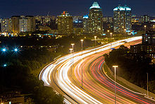 Bird's-eye view of a highway at night. The highway starts at the bottom centre, turning to the right as it progresses into the background. Streams of light show the movement of cars along the highway. Tall poles support lit bulbs. Many buildings and lights are visible in the distance.