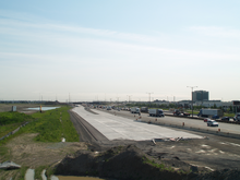 """""""A paved segment of highway next to a busy freeway."""""""