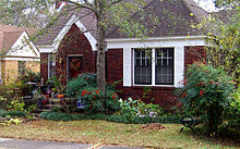 Small, one-story brick-faced house with small yard in front