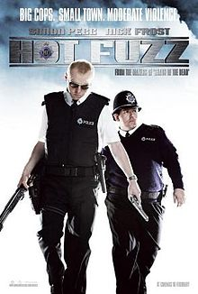 Film poster of two men dressed as British police officers. The man on the left is looking down and is holding a shotgun and a handgun. The man on the right is looking to his left and is located behind the first man. The poster includes the film's title, tagline, and starring roles.