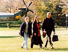 Man, same woman, and teenage girl walk across lawn after leaving a helicopter
