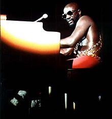 An adult male with sunglasses plays a piano under a spotlight on a darkened stage, 1973