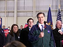 Mitt Romney surrounded by people, holding a microphone and smiling