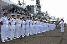 Japanese sailors lined up on a quay in front of a warship.