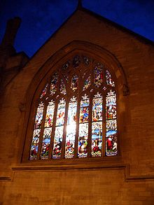 A night scene of a stained glass window lit from inside