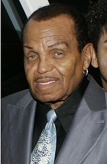 A mature African American man wearing a grey suit, black shirt and light blue tie. His hair is short and he wears a hooped earring in his right ear.