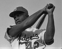 """A man swings a bat; he is wearing a dark cap with a """"B"""" on it and a jersey with the word """"Dodgers"""" on his chest."""