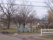 an image of a park. Many large trees are around the park and at the entrance a sign say Junge Park. Two basketball hoops and a baseball diamond are visible.