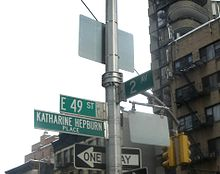 """A street sign that reads """"E 49 St"""", with another underneath it that reads """"Katharine Hepburn Place""""."""