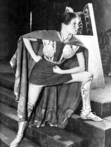 Young woman, dressed in a short tunic and armour, acting in a play.