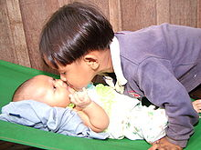 On the right a young boy of asiatic appearance with a pudding basin haircut, leans over a baby lying on its back on the left. The boy and baby are touching noses. The baby gazes up at the boy with an expression of intense interest.
