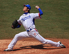 """A man in a white baseball jersey with """"KOREA"""" on the chest in blue and """"17"""" on his leg in orange pitches a baseball from the pitcher's mound with his left hand. He is wearing a black baseball glove on his right hand."""