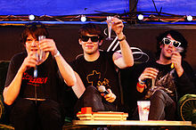 Three men who are raising glasses. They are wearing dark clothing