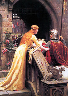 A young woman in a medieval-style dress of cream satin ties a red scarf to the arm of a man in armour and mounted on a horse. The scene is set at the portal of a castle.