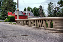 """A small concrete bridge crosses a stream.  The sides of the bridge were designed to spell out """"Lincoln Highway""""."""