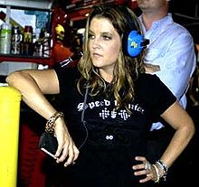 A woman in a black T shirt holds her left hand on her hip, while leaning against a chest-height surface with her right elbow. She is wearing blue headphones and looks towards her right.