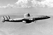 A monochrome photograph of a large aircraft flying above dimly-visible land, below white clouds, the aircraft showing multiple engines, three vertical tail surfaces and a large, rounded radar structure on its upper surface above and between the wings