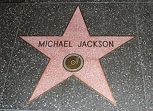 """A pink star with a gold colored rim and the writing """"Michael Jackson"""" in its center. The star is indented into the ground and is surrounded by a marble colored floor."""