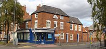 The corner of a terraced street in a suburban setting. The lower storey is a corner shop, advertising as a chiropractic clinic. The building is two storeys high, with some parts three storeys high.