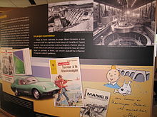 An exhibit illustrating the impact of the Manic-Outardes hydroelectric project with a car, a Hergé drawing of Tintin, a paperback, a picture of a man filming an action scene, a videocassette box, a stamp and a sports car.