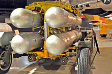 Four silver B28FI nuclear bombs in a rack ready for loading into an aircraft.