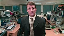 A man in a suit which some computers and shelves behind him