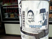 Partially ripped poster of a veiled woman and a man. Chinese text line its vertical edges while Indonesian text is written in the middle.
