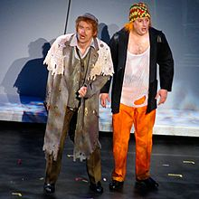 Two men in torn clothes stand on a stage: the man on the left is wearing a long coat and has a hat on, the man on the right wears a chequered hat, a string vest, jacket and orange trousers