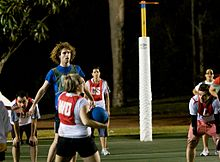 Woman holding a netball while other players stand watching her. Woman and shooting team is wearing white with red bibs. Opposing team is wearing blue with green bibs.