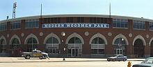 A large brick stadium with many round windows on the bottom and many rectangle windows in groups of four line the top of the stadium. The words Modern Woodmen Park are displayed above the door