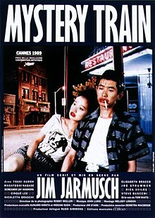 A young Japanese couple are sitting on a dimly-lit street outside a restaurant with a neon sign. The woman is looking off camera and resting against the man, who is downcast with a cigarette in his mouth; both are wearing bright red lipstick. Superimposed above the couple is the title MYSTERY TRAIN, with credits in French at the bottom of the image.