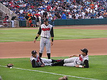 """Three men wearing black caps and gray baseball uniforms with """"Nashville"""" written across the chest in red letters on a baseball field before a game"""