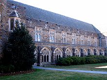 A Gothic-style exterior showcases Cathedral-like windows with intricate framework and dark, colorful stone, with bushes and grass in the foreground