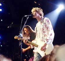 A blonde man wearing a white shirt with flowers plays a white guitar and sings, while in the background another man plays the bass.