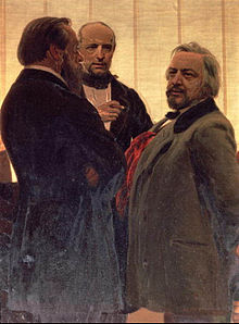 Three men standing together - two men with beards, the one on the right with grey hair, flanking a third man watching them intently