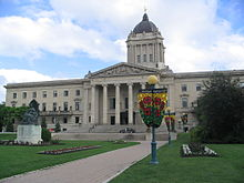 A large concrete building with Classical-style columns and a green dome topped by a golden statue