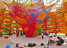 A weblike structure in many bright colors with several pendulous appendages hanging from it, itself hanging from the textile roof of an open wooden structure. There are children playing with the pendulous appendages and seated around the side, where many backpacks and shoes have also been left