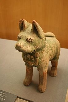 A green-glazed ceramic statuette of a dog with pointy ears and curly tail, standing upright on all fours with eyes open